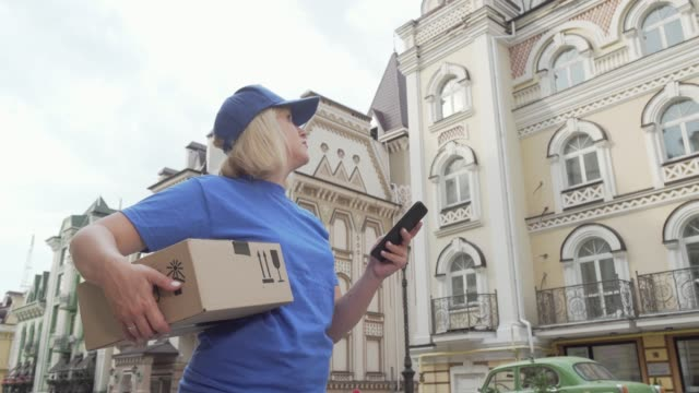 Delivery woman with parcel box using smart phone online map Delivery woman with parcel box using smart phone online map. Low angle shot of a female delivery service courier looking for the house of a client on city street. Shipping concept post office stock videos & royalty-free footage