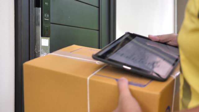 vídeos de stock e filmes b-roll de delivery worker delivers packages - cardboard box