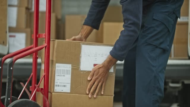 delivery worker stacking packages onto the cart and pulling it away - attività fisica video stock e b–roll