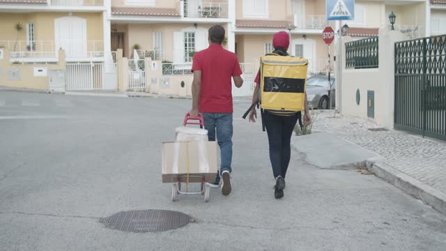 Delivery workers carrying food, wheeling cart