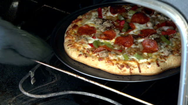 deluxe pizza inside a stove or oven Getting a pizza out of the oven or stove. Deluxe pizza with pepperoni,peppers,c heese, meat balls and onions. Home cooking of fast food. positioning stock videos & royalty-free footage