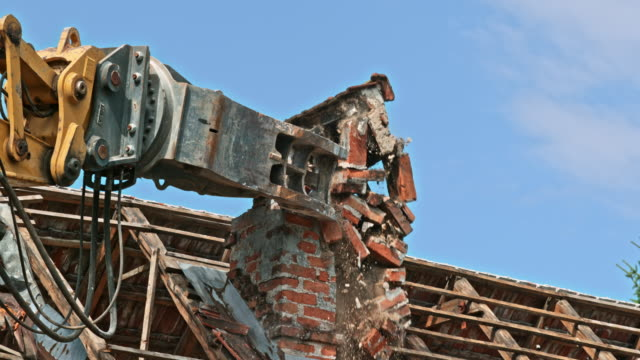 SLO MO Demolition excavator tearing down an old brick chimney