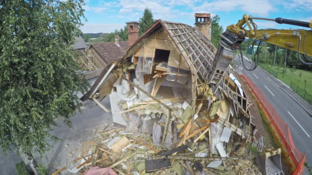 TIME LAPSE Demolition excavator tearing down an old house Time-lapse of a demolition excavator demolishing an old house in the suburbs. Shot in Slovenia. demolishing stock videos & royalty-free footage