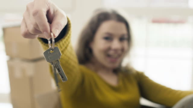 Demonstaring keys from new house in close-up Woman sits inside empty box and shows a keys from a new house on camera. Happy woman smiles and grimacing moving the keys in front of camera. Adult woman just relocate in new house sits among unpacked boxes with things at blurred background. hanging stock videos & royalty-free footage