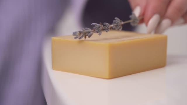 A demonstration close-up video of woman's hand putting a lavender inflorescences on the piece of handmade soap