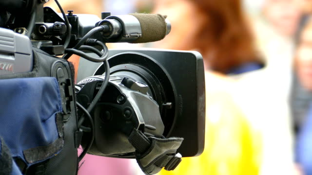 demonstration durch die tv-kamera im vordergrund - journalist stock-videos und b-roll-filmmaterial