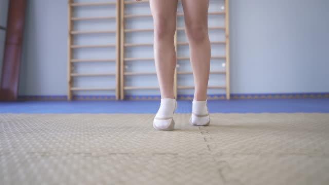 en demonstrations video av en liten gymnast i pointe skor gå på tå över sport matta - på tå bildbanksvideor och videomaterial från bakom kulisserna