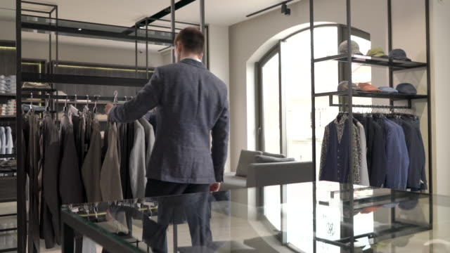 A demonstration video of a man looking at stylish grey jacket in showroom of men clothing boutique. Brand male suits video