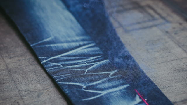 Denim Jeans Laser Engraving. Manufacturing Denim. Ripping Jeans with a Laser Machine at Clothing Factory. Garment Manufacturing.