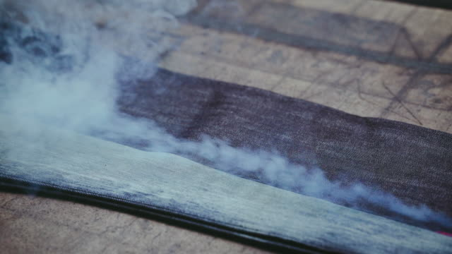 denim jeans laser engraving. manufacturing denim. ripping jeans with a laser machine at clothing factory. garment manufacturing. - cucitura video stock e b–roll