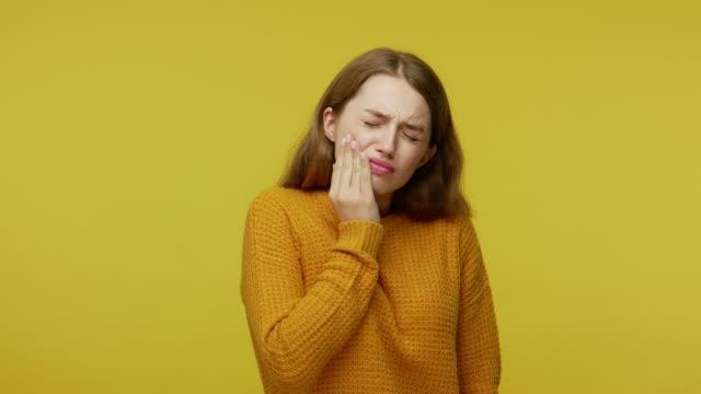 vídeos de stock e filmes b-roll de dental health. sick unhappy girl closing eyes in pain and holding cheek, frowning suffering severe toothache - boca suja