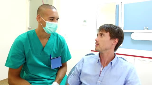 tandläkare undersöker tänderna av en manlig patient - two dentists talking bildbanksvideor och videomaterial från bakom kulisserna
