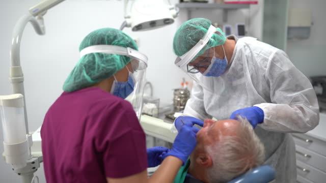 diş hekimi ofisinde diş prosedürü gerçekleştiren diş ekibi - diş sağlığı stok videoları ve detay görüntü çekimi