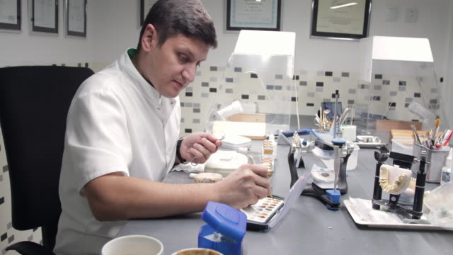 Dental technician colouring veneers with spatula Dental technician choosing colour for pigmentation of veneers with spatula implant stock videos & royalty-free footage