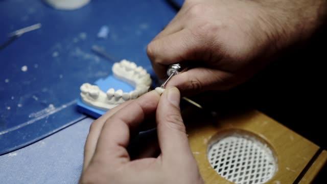 diş teknisyeni bir hasta için sıfırdan yeni dişleri yapma. diş hekimi diş diş aletleri kullanarak ile diş diş bürosu'nda düşük ışık sabitleme. diş hekimi diş hazırlanıyor. - diş sağlığı stok videoları ve detay görüntü çekimi