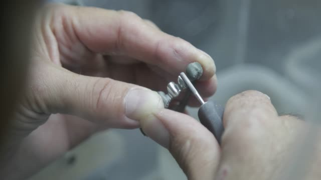 Dental technician refining dental bridge with a rotary file Dental technician cleaning a metal dental bridge working with a rotary file, holding it in one hand implant stock videos & royalty-free footage