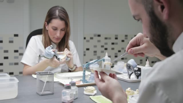 Técnicos dentales poner puente dental sobre un pilar del modelo - vídeo