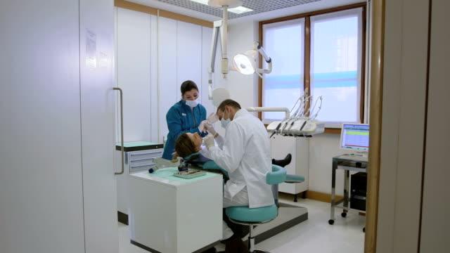 vídeos y material grabado en eventos de stock de dentista y asistente control higiene dental de cliente femenino - ortodoncista