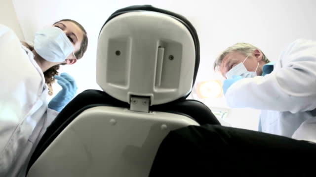 Dentist and his nurse prepare to treat patient, smiling and reassuring as they take out their instruments. video