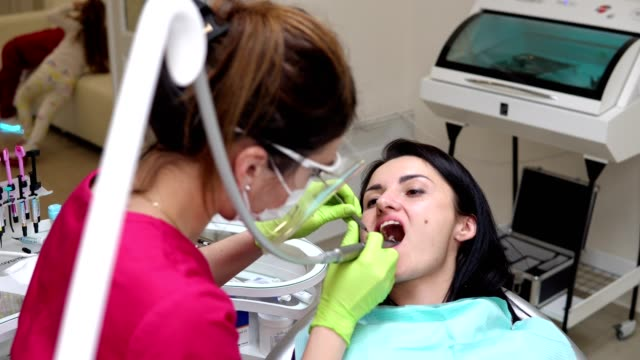 dentist cleans woman's teeth with professional toothpaste and automatic brush. dentist using saliva ejector or dental pump to evacuate saliva. - orthodontist stock videos and b-roll footage