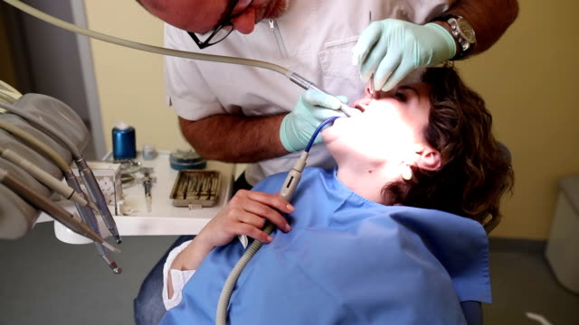 Dentist curing a female patient, handheld shot video