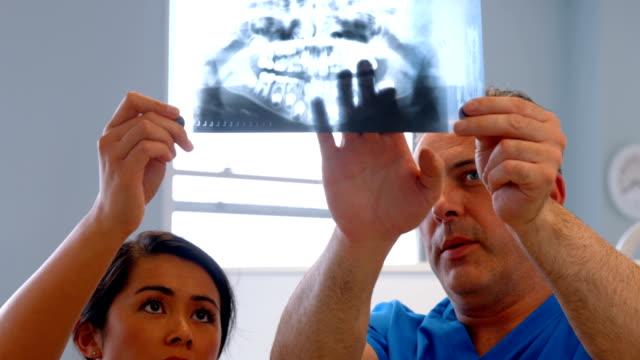 Dentista discutiendo xray los dientes - vídeo