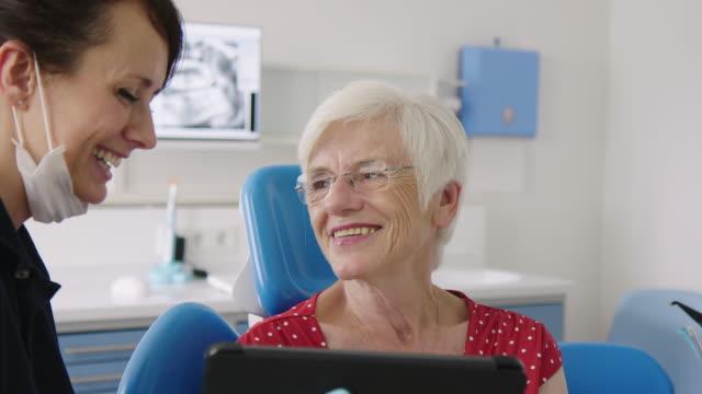 tandläkare diskuterar testresultat med kvinnan - two dentists talking bildbanksvideor och videomaterial från bakom kulisserna