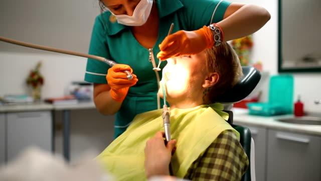 Dentista examinar los dientes de un paciente en el dentista. - vídeo