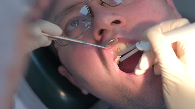 Dentist examining patient gums with probe using method of computer diagnostics. video