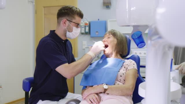hastanede kıdemli kadının dişlerini inceleyerek dişçi - diş sağlığı stok videoları ve detay görüntü çekimi
