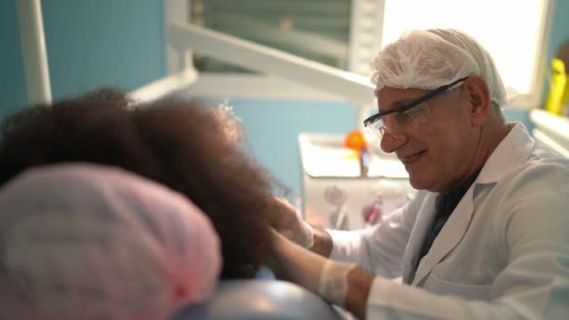 Dentist examining teeth of child sitting in dentist chair
