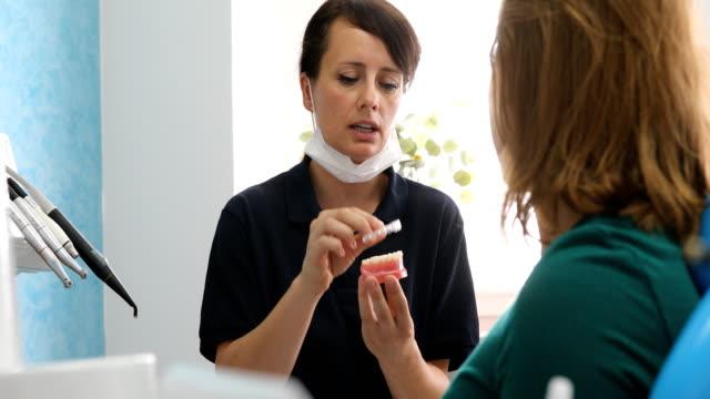 Dentist explaining orthodontic silicone trainer implant to patient