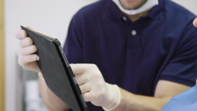 vidéos et rushes de dentiste expliquant le patient au-dessus de la tablette numérique - expliquer