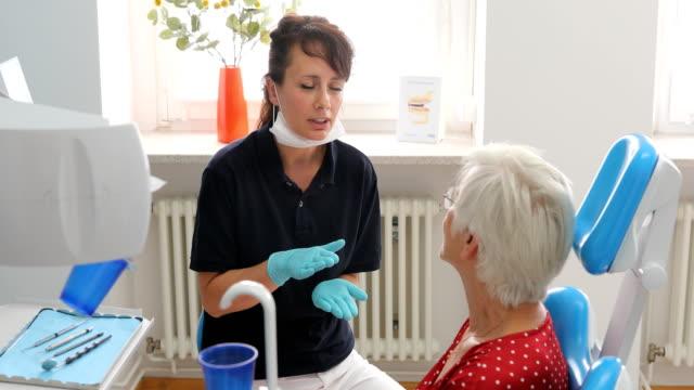 tandläkare som förklarar behandlingen för patienten - two dentists talking bildbanksvideor och videomaterial från bakom kulisserna