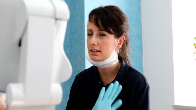 vídeos y material grabado en eventos de stock de dentista explicando el tratamiento al paciente - ortodoncista