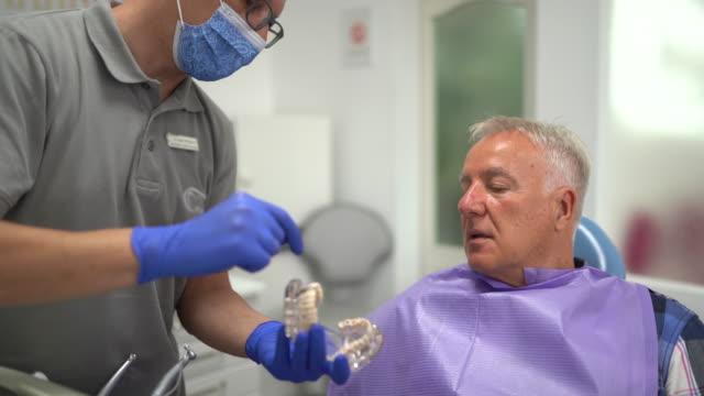tandläkare som håller protes och pratar med patienten på tandläkarens kontor - two dentists talking bildbanksvideor och videomaterial från bakom kulisserna