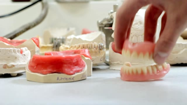 Dentist prosthetist takes a denture from the working table video