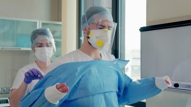 stockvideo's en b-roll-footage met tandarts die beschermende kleding in tandartsbureau zet - buiten de vs