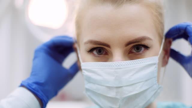 stockvideo's en b-roll-footage met tandarts die op beschermend masker vóór chirurgie zet - mirror mask