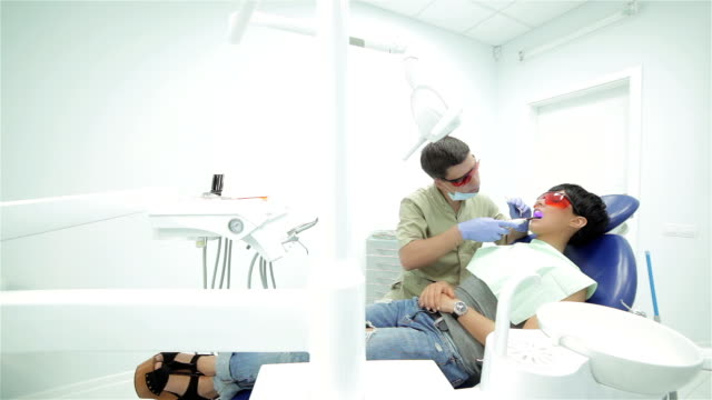Dentist shines ultraviolet photopolymer seal on fixing it video