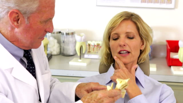 Dentista mostrando paciente do sexo feminino modelo de Osso Maxilar - vídeo