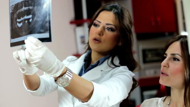 Dentista mostrando paciente do sexo feminino raios-x - vídeo