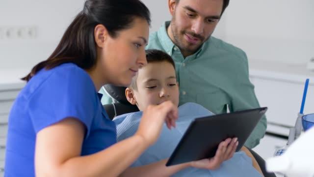 歯科医院で子供にタブレット pc を示す歯科医 - 歯科点の映像素材/bロール