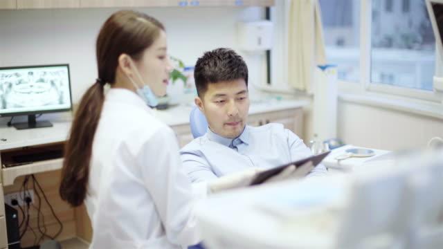 tandläkare som visar tänder x-ray till sin patient - two dentists talking bildbanksvideor och videomaterial från bakom kulisserna