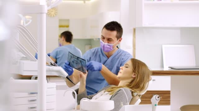 tandläkaren visar röntgen till kvinna - two dentists talking bildbanksvideor och videomaterial från bakom kulisserna