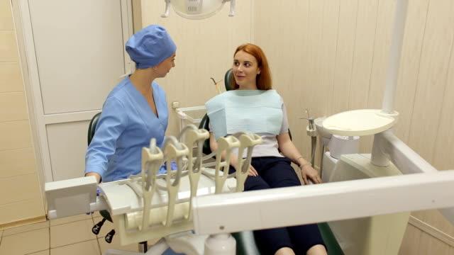 tandläkare att prata med en tjej patient på kliniken. - two dentists talking bildbanksvideor och videomaterial från bakom kulisserna