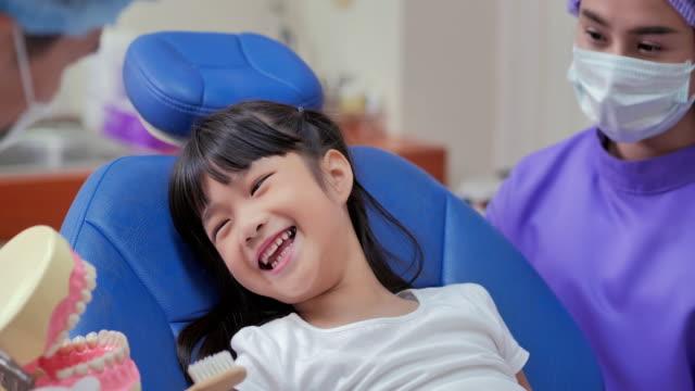 vídeos y material grabado en eventos de stock de dentista enseñando a la niña cómo cepillarse los dientes. linda niña sentada en la silla dental y teniendo tratamiento dental. concepto de medicina, estomatología y atención médica. chequeo dental, tecnología, educación, concepto de personas. - ortodoncista