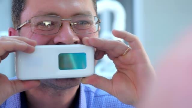 Dentist testing man's teeth using UV scanner in dentistry, portrait closeup. video