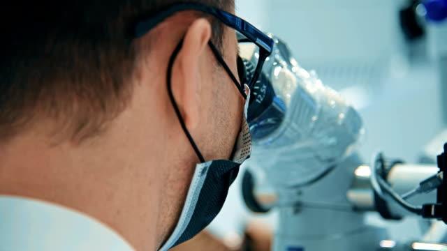 vídeos y material grabado en eventos de stock de dentista usando microscopio dental - guante quirúrgico