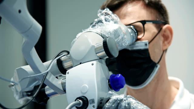 vídeos y material grabado en eventos de stock de dentista usando microscopio - guante quirúrgico